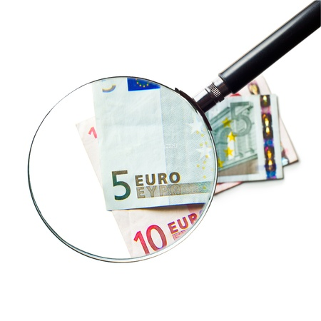 the euro currency under a magnifying glass  on white background photo