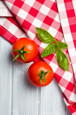 fresh basil leaves and tomatoes on kitchen table photo