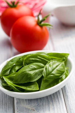 fresh basil leaves and tomatoes on kitchen table Stock Photo - 14512892