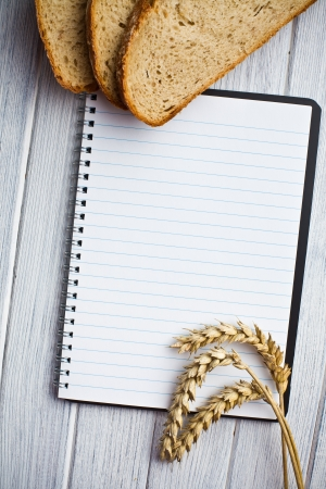 blank notebook with bread and wheat on wooden table photo