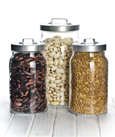various legumes in the jars on white table photo