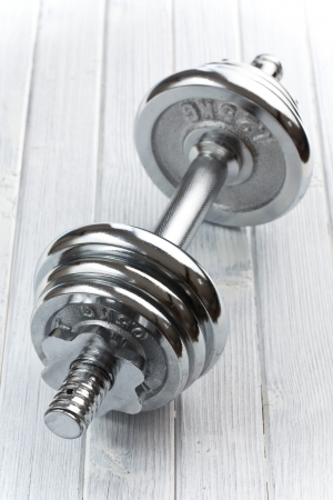 Chromed fitness dumbbell on white floor photo