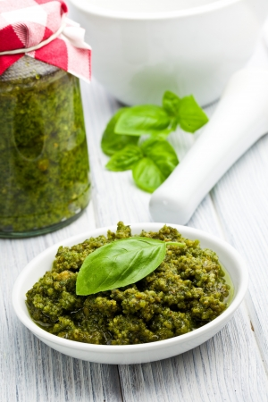 basil pesto in ceramic bowl on kitchen table photo