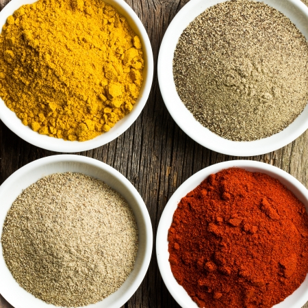 various colored spices in ceramic bowls photo
