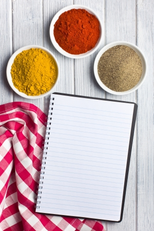 recipe book: various colored spices with blank recipe book  studio shot  Stock Photo