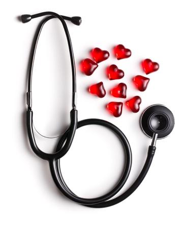 estetoscopio corazon: estetoscopio y corazones rojos sobre fondo blanco Foto de archivo