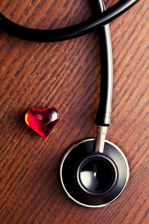 stethoscope and red heart on wooden table photo