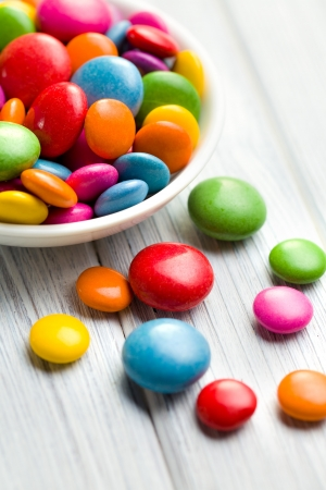 the colored candy in white bowl photo