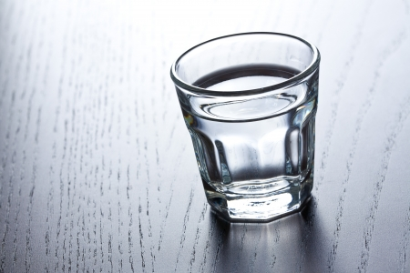 shot glass: glass of clear alcohol on wooden table Stock Photo