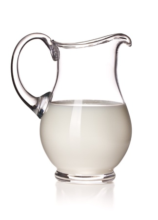 milk in a glass pitcher on white background photo