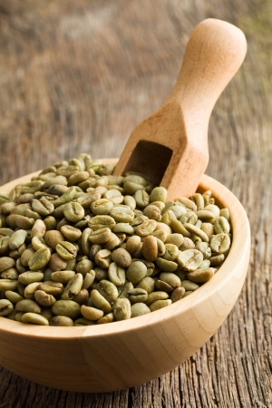 unroasted: green coffee beans with wooden scoop  in wooden bowl