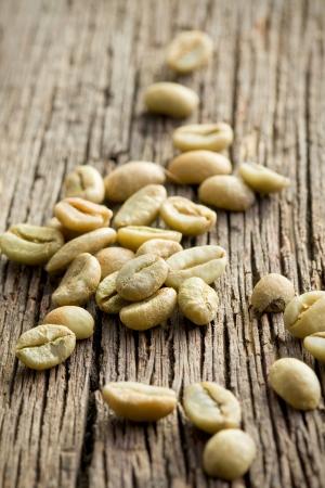 ejotes: granos verdes de caf� en la mesa de madera vieja