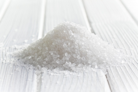 minerals food: white crystal salt on wooden table