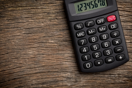 calculate: the calculator on old wooden table