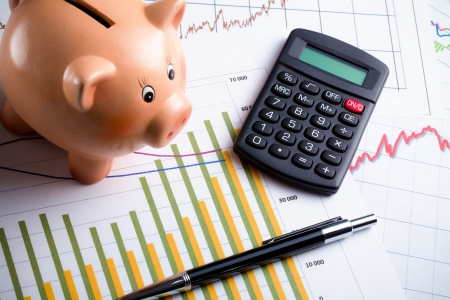 Calculator, piggy bank and pen on business graph. Business concept. photo