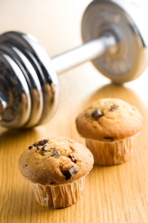 Diet concept. Muffin and dumbbell on background. photo