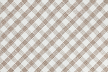 Photo shot of beige checkered fabric. Tablecloth texture