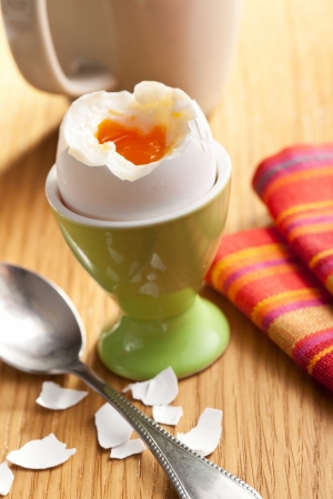 boiled egg in eggcup on wooden table photo