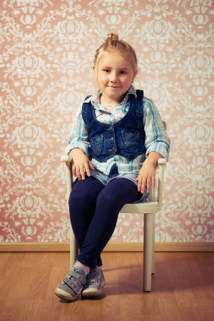 girl sit: little girl sitting on retro chair Stock Photo