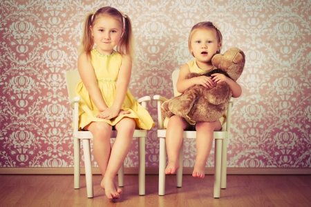 two sisters sitting on a retro chair photo