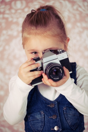 young girl in studio with analogue camera  photo