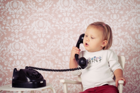 little baby with old vintage phone before retro background photo