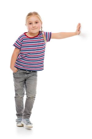 cool kids: Little girl leaning against a white wall. Studio shot. Stock Photo