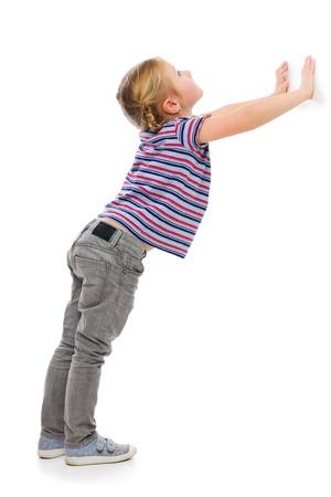 cool girl: Little girl leaning against a white wall. Studio shot. Stock Photo
