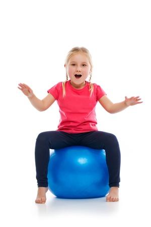 large ball: Little girl doing fitness exercise with gym ball. Studio shot.