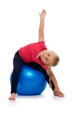 ball stretching: Little girl doing fitness exercise with gym ball. Studio shot.