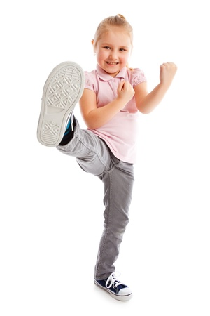 youngster  girl: Little girl kick by foot. Studio shot.  Stock Photo