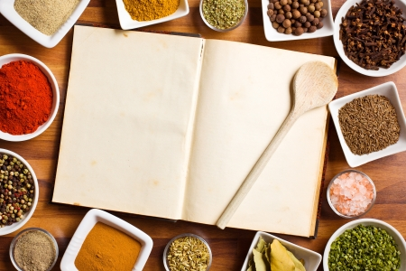 The cookbook and various spices and herbs. Stock Photo