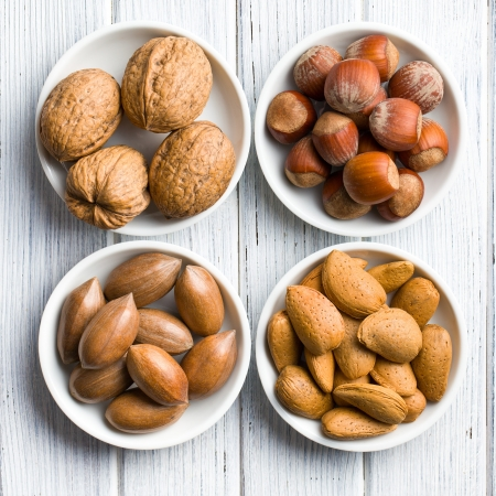 mixed nuts: various nuts in ceramic bowls on woden table