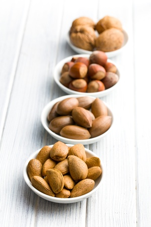 various nuts in ceramic bowls on woden table photo
