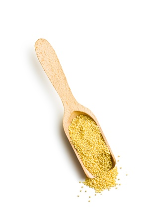 millet: millet in wooden scoop on white background