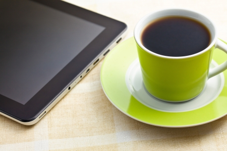 the black coffee in green cup with computer tablet photo