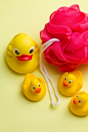 squeak: yellow bath ducks and bath puff on color background Stock Photo