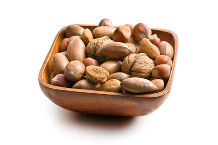 various unpeeled nuts in wooden bowl on white background photo