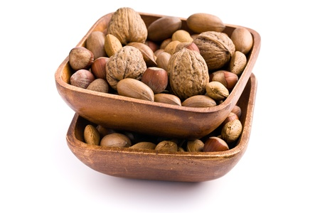 unpeeled: various unpeeled nuts in wooden bowl on white background Stock Photo