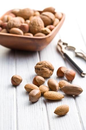 unpeeled: various unpeeled nuts on wooden table