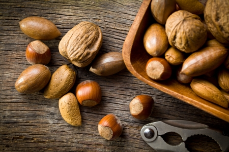 whole pecans: the various unpeeled nuts in wooden bowl