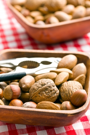 unpeeled: various unpeeled nuts in wooden bowl