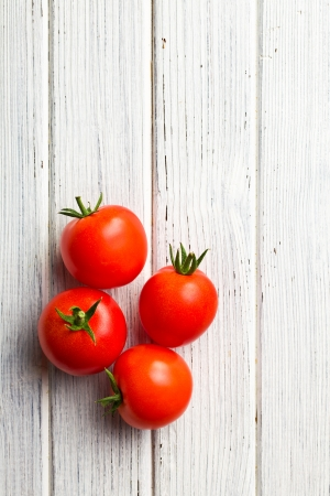 top view of red tomatoes on wooden table photo