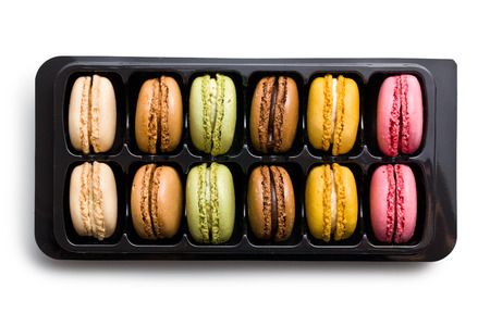 colorful macaroons in plastick box on white background photo