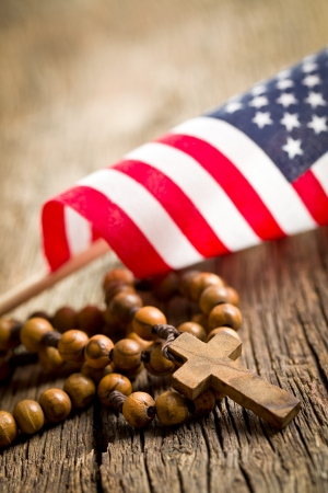 sacrosanct: rosary beads with american flag on wooden background Stock Photo