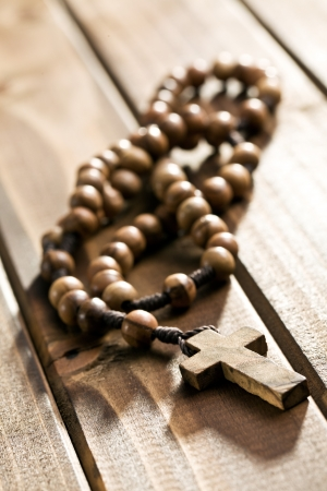 rosary beads lying on wooden background photo