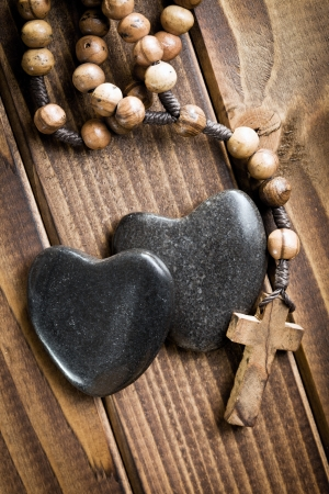 top view of stone hearts with rosary beads on wooden background photo