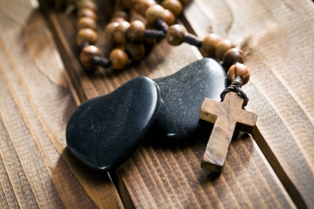 stone hearts with rosary beads on wooden background photo