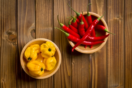 top view of red peppers and habanero in bowls on wooden table photo