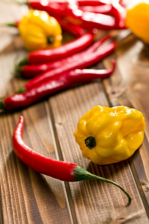 red chili peppers and yellow habanero on wooden background photo
